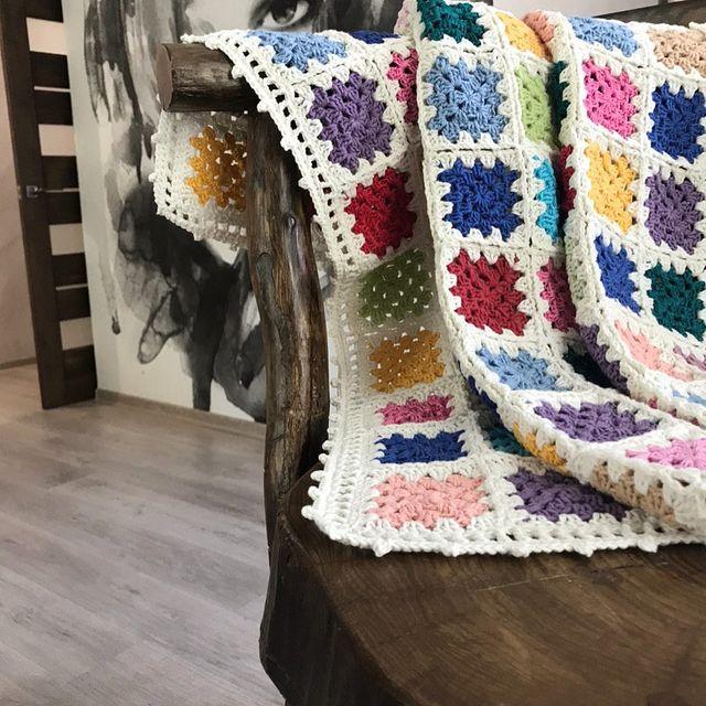 Multicolored granny square blanket with a white border